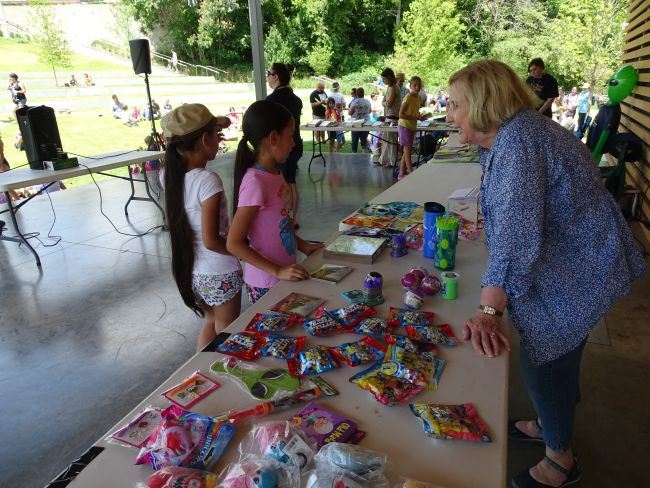 Woman giving prizes at a table to children on the stage at the Memorial Park