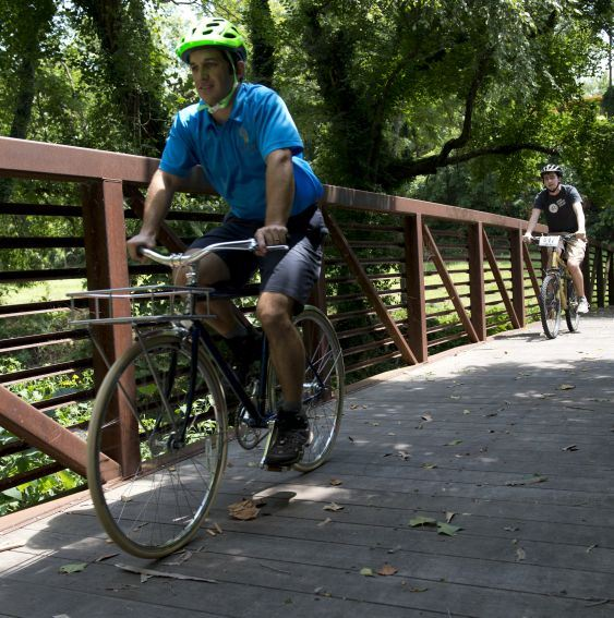 man bicyling on bridge in park