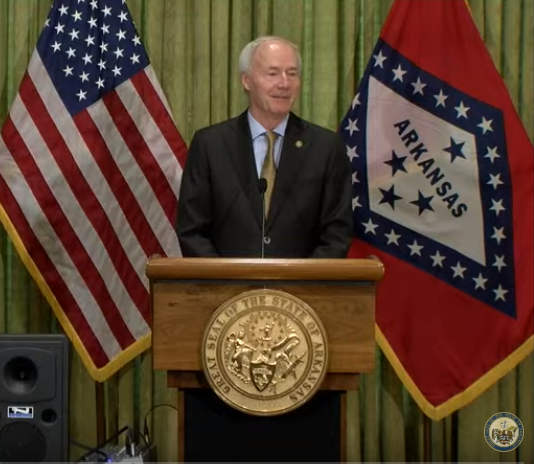 Governor Asa Hutchinson standing at a podium with the Arkansas and US Flags behind him