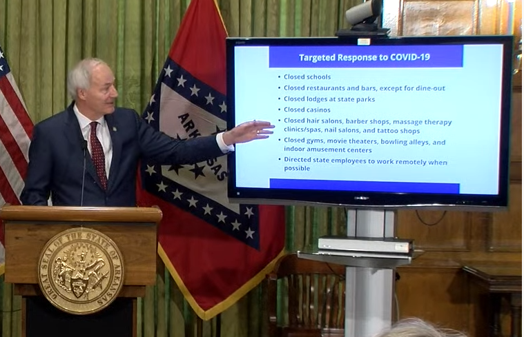 Governor Hutchinson standing at a lectern pointing to a TV monitor