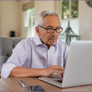 older man sitting at a wooden table with a laptop
