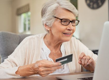 Senior woman sitting in front of a computer holding a credit card