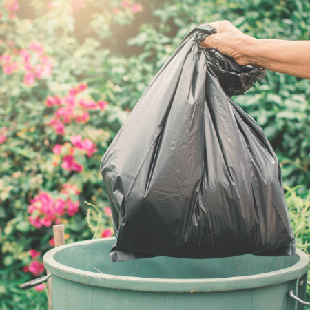 person holding a black trash bag against a backdrop of a garden