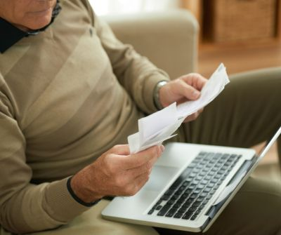 man holding papers while sitting with laptop on his lap on the couch