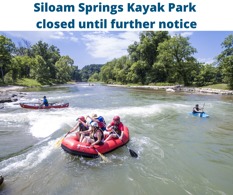 four people on a raft at the Siloam Springs Kayak Park