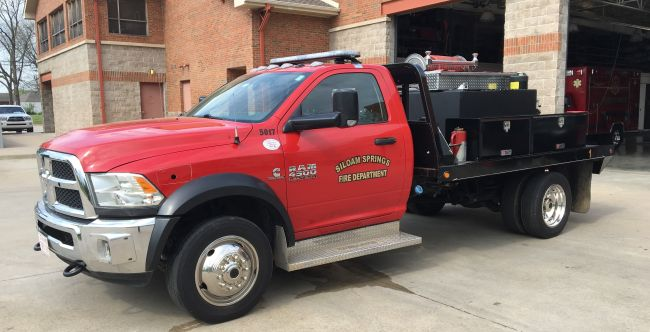 Brush Fire Truck red cab with black bed with Siloam Springs Fire Department on the drivers door